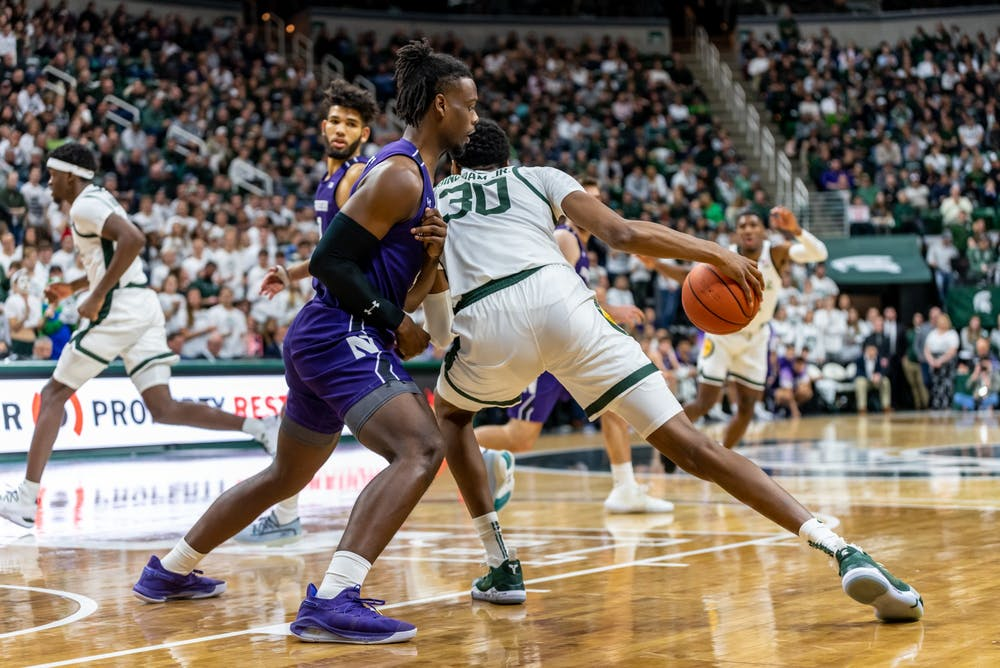 <p>Sophomore forward Marcus Bingham Jr. (30) backs down Northwestern's Jared Jones (left). The Spartans defeated the Wildcats, 79-50, on Jan. 29, 2020 at the Breslin Student Events Center. </p>