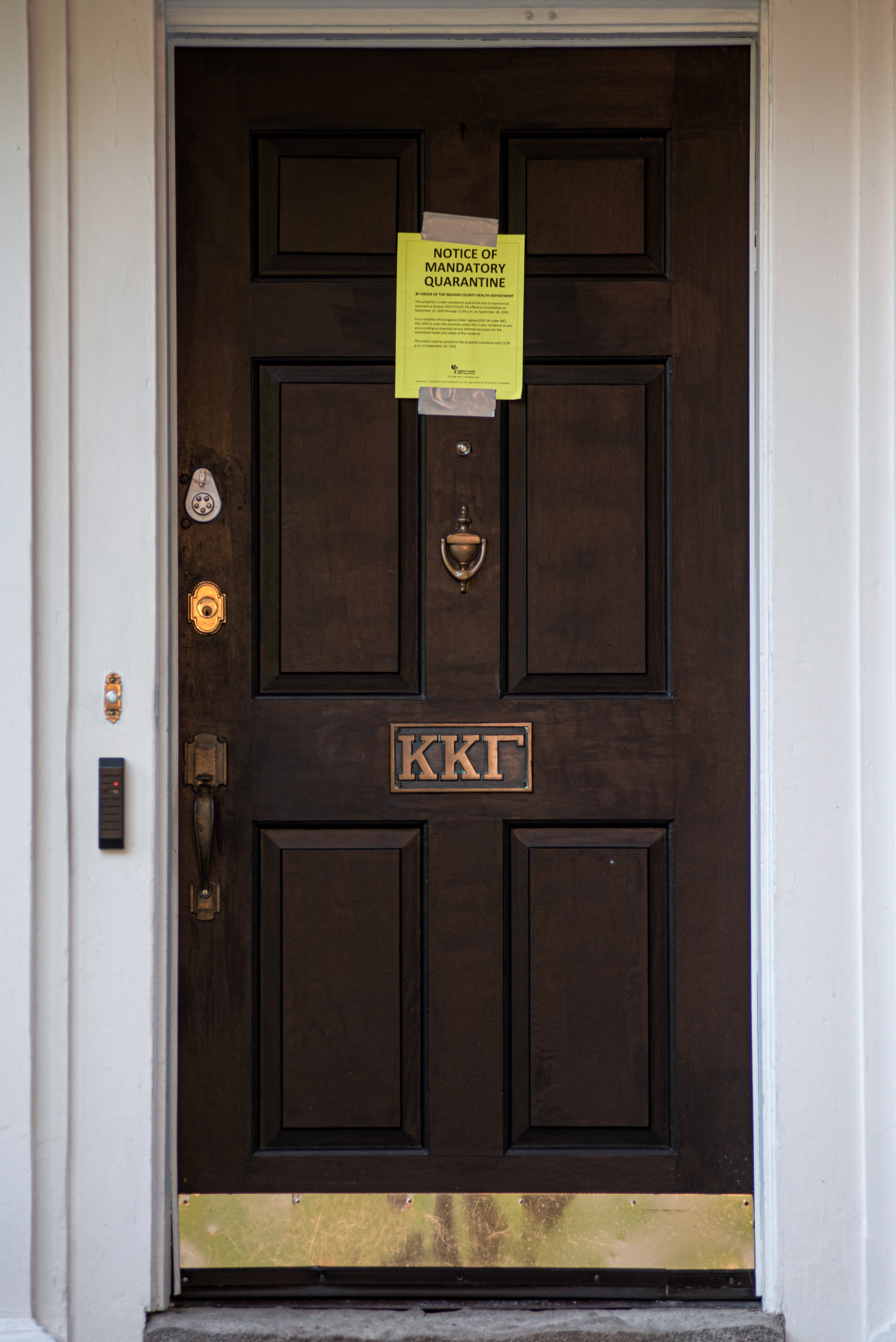 A yellow piece of paper that reads 'Notice of mandatory quarantine' is taped to the front of a wooden door. On the door are three Greek letters.