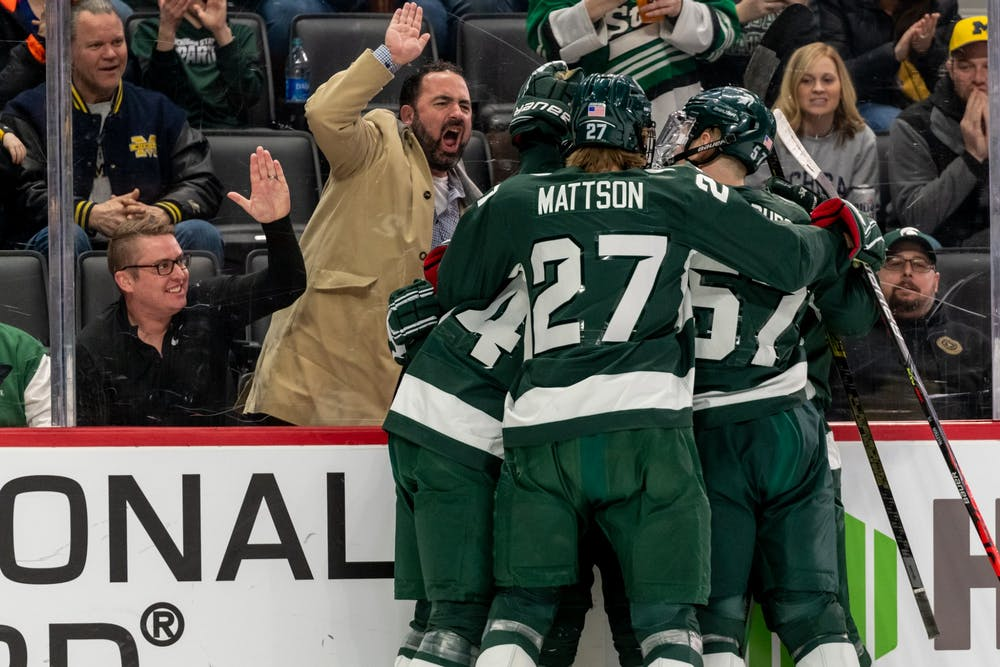 <p>Spartan hockey players celebrate a goal from sophomore defenseman Dennis Cesena.</p>