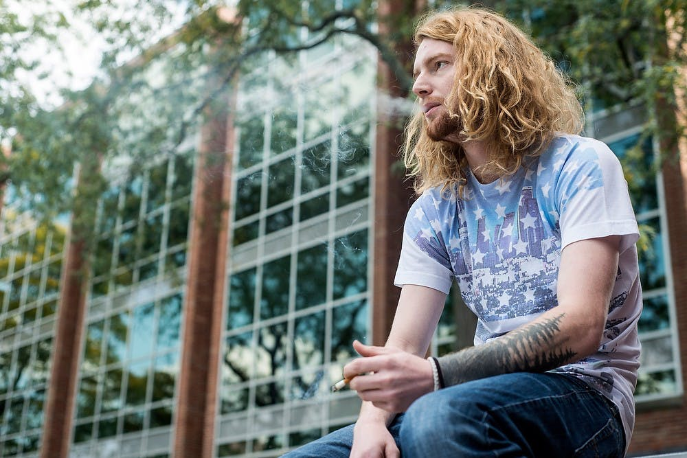 <p>Advertising junior Chris TeBeau takes a cigarette break Sept. 29, 2014, between studying outside of the Main Library. Erin Hampton/The State News</p>