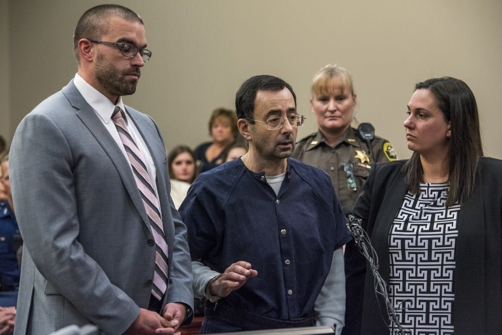Ex-MSU and USA Gymnastics Dr. Larry Nassar raises his hand on the seventh and final day of his sentencing on Jan. 24, 2018 at the Ingham County Circuit Court in Lansing. (Nic Antaya | The State News)