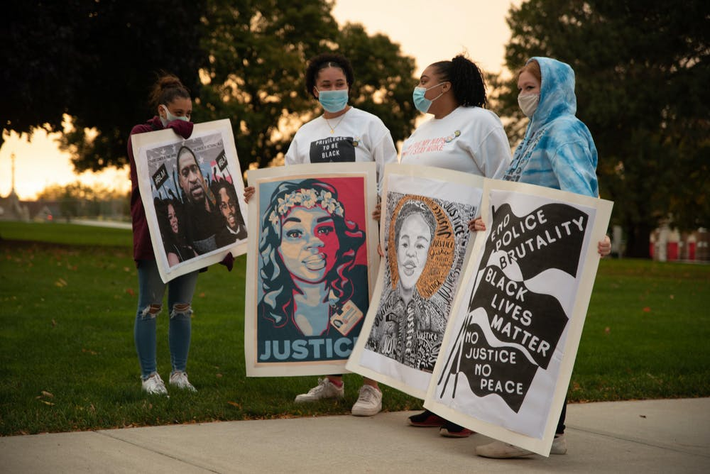 <p>7 Miles for 7 Shots March participants holding &quot;Justice for Breonna&quot; signs at the Michigan State Capital on Friday, October 16, 2020. </p>