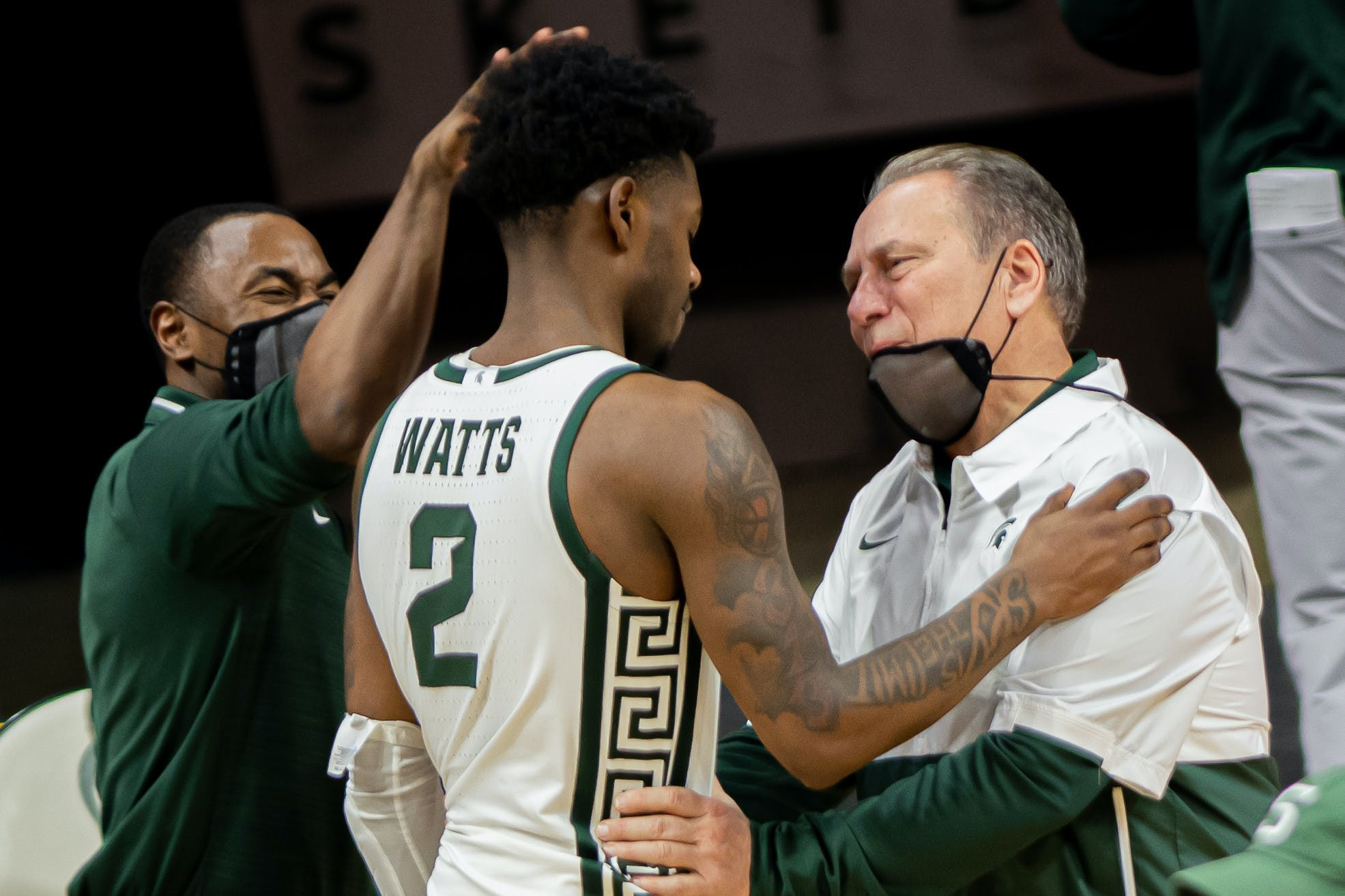 A person wearing an MSU basketball jersey embraces a person wearing a face mask while another person pats their head.
