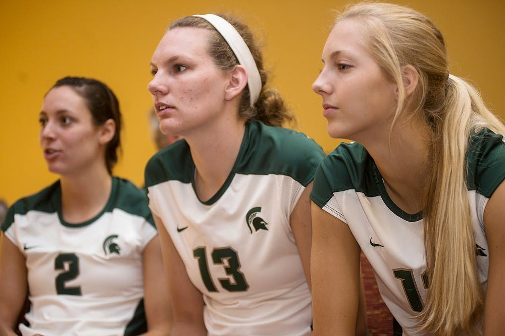 <p>Redshirt sophomore defensive specialist Kristen Muir, left, redshirt freshman middle backer Brooke Kranda and freshman setter Rachel Minarick talk with their teammates during volleyball media day at  Spare Time Entertainment Center in Lansing on August 22, 2014. Erin Hampton/The State News</p>