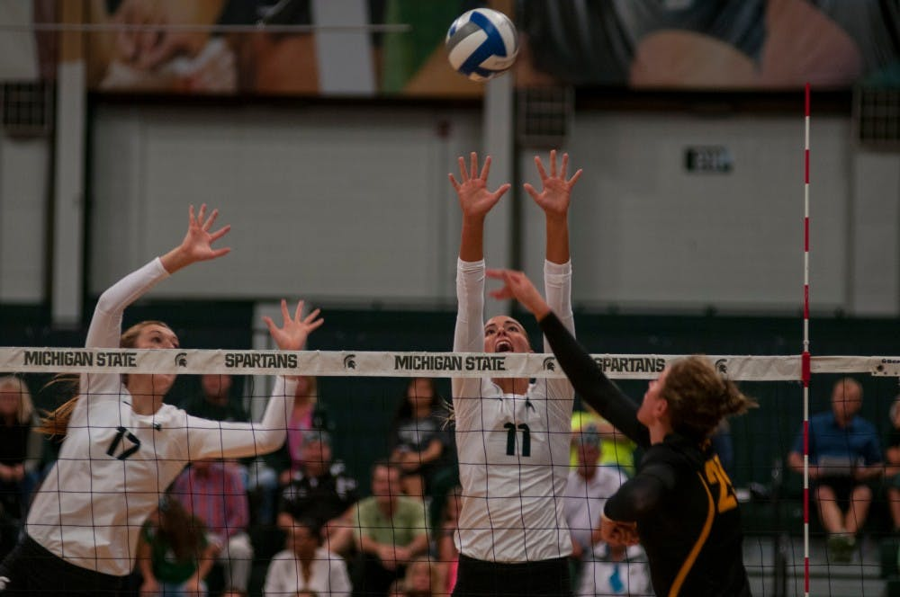 Senior outside hitter Chloe Reinig (11), right, and junior middle blocker Alyssa Garvelink (17) attempt to block the ball during the volleyball game against the University of Iowa on Sept. 23, 2016 at Jenison Field House. The Spartans defeated the Hawkeyes, 3-0.
