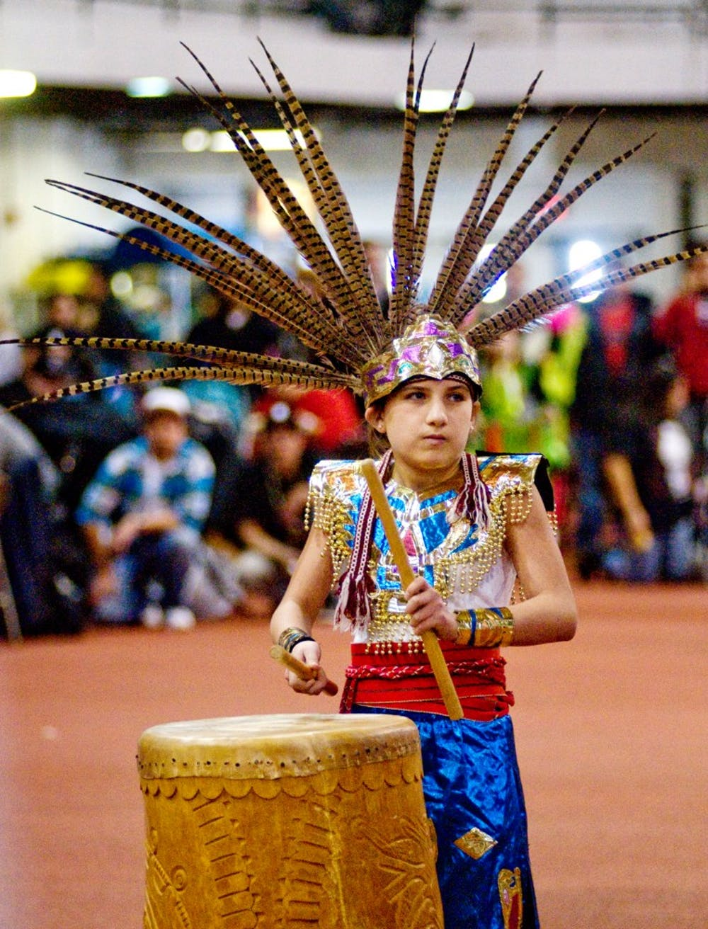 Reina Torrez-Miner, 12, plays a drum Saturday at Jenison Field House. Torrez-Miner was leading Dance Azteca, a group that dances in traditional Mexica style, an indigenous people from Mexico. The group was participating in the 28th annual Pow Wow of Love. Matt Radick/The State News