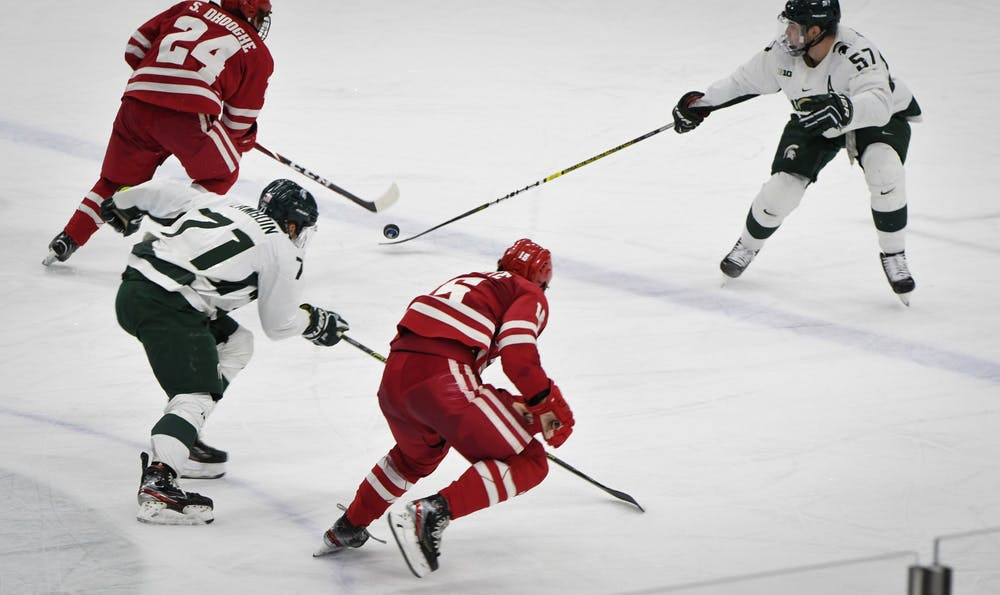Redshirt senior defender Jerad Rosburg (57) and senior forward Logan Lambdin (71) fight for the puck during the game against Wisconsin at the Munn Ice Arena on December 6, 2019. The Spartans defeated the Badgers 3-0.