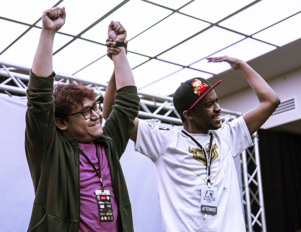 No. 1 MKLeo (left) celebrates his Grand Finals win onstage with No. 22 Dark Wizzy (right) at Frostbite 2020.