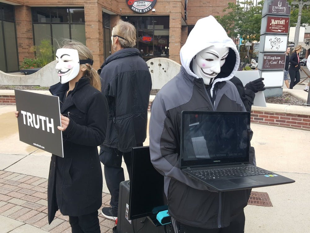"""Members of Anonymous for the Voiceless, an animal rights and welfare organization, form a """"cube of truth"""" outside of the East Lansing Marriott on Sunday, October 29 2017."""