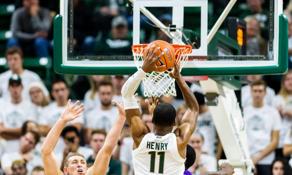 <p>Sophomore forward Aaron Henry (11) dunks over Albion defenders. The Spartans defeated the Britons, 85-50, on Oct. 29, 2019 at the Breslin Student Events Center.</p>