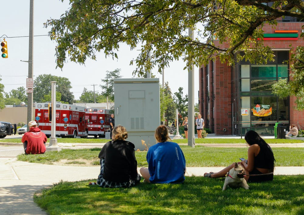 <p>Hub residents, including Sydney Hodges (middle), Riley Modlin (right) and her dog Frankie, find shade as they wait to be allowed back into the building. &quot;I&#x27;m honestly just really confused, they don&#x27;t tell us anything,&quot; Hodges said. Image was taken just outside of the Hub on July 26, 2021.</p>