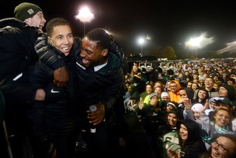<p>Then-senior guard/forward Branden Dawson (right) holds onto then-senior guard Travis Trice after shouting to the crowd he and Trice would crowd surf Oct. 17, 2014, during the Izzone Campout at Munn Field. Hundreds of students battled the cold and rain to sleep outdoors overnight in hopes of getting lower bowl seating. Julia Nagy/The State News</p>