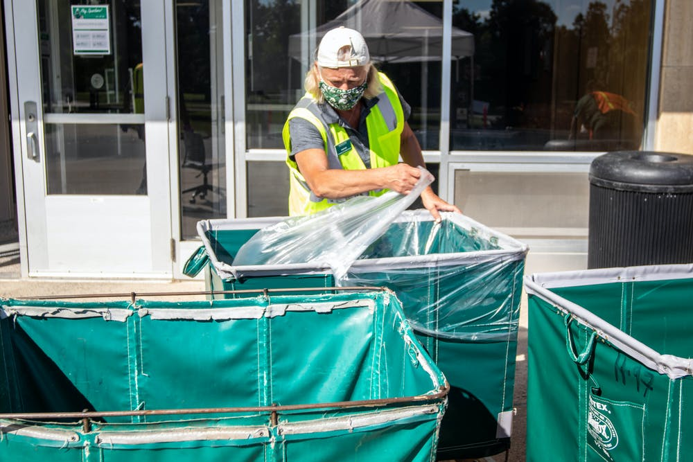 People sanitize carts at Wilson Hall during move in Aug. 31, 2020.