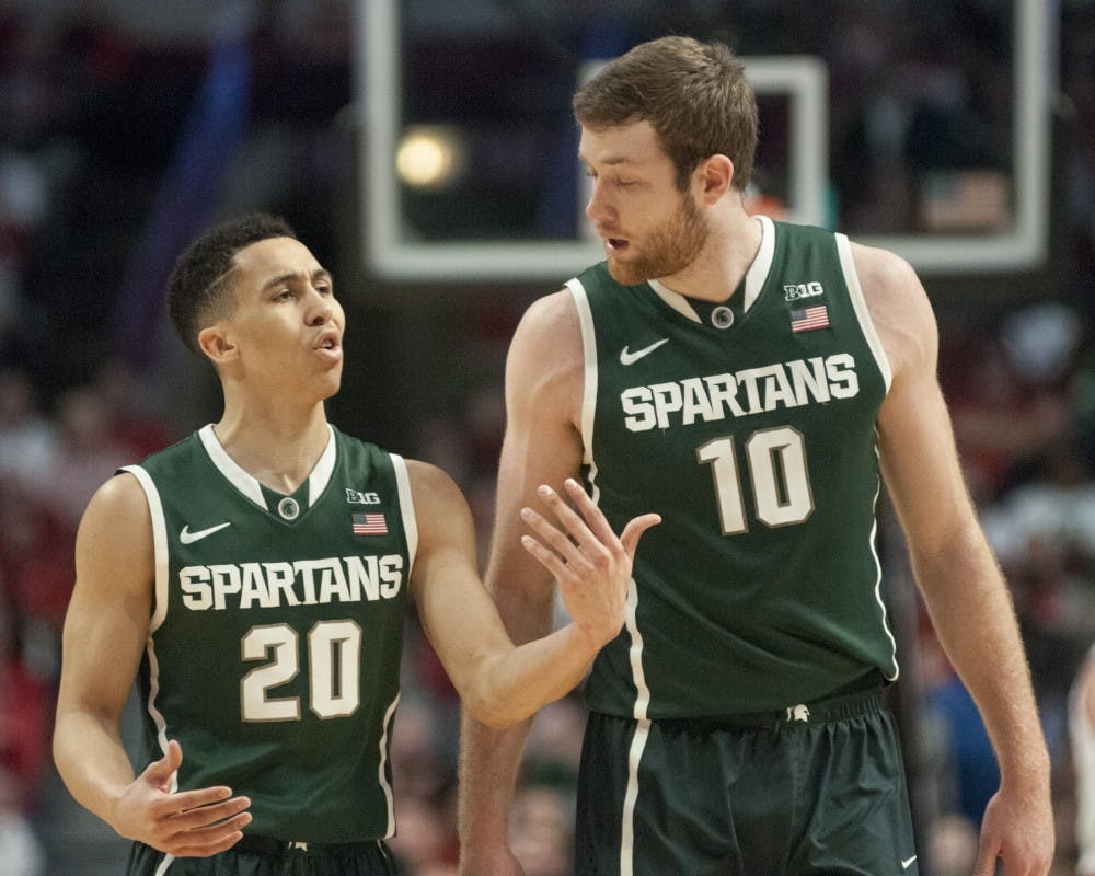 <p>Senior guard Travis Trice and junior forward Matt Costello make their way off the court Mar. 15, 2015, during a timeout in the championship game of the Big Ten Tournament against Wisconsin at United Center in Chicago. The Badgers defeated the Spartans in overtime, 80-69. Kelsey Feldpausch/The State News</p>