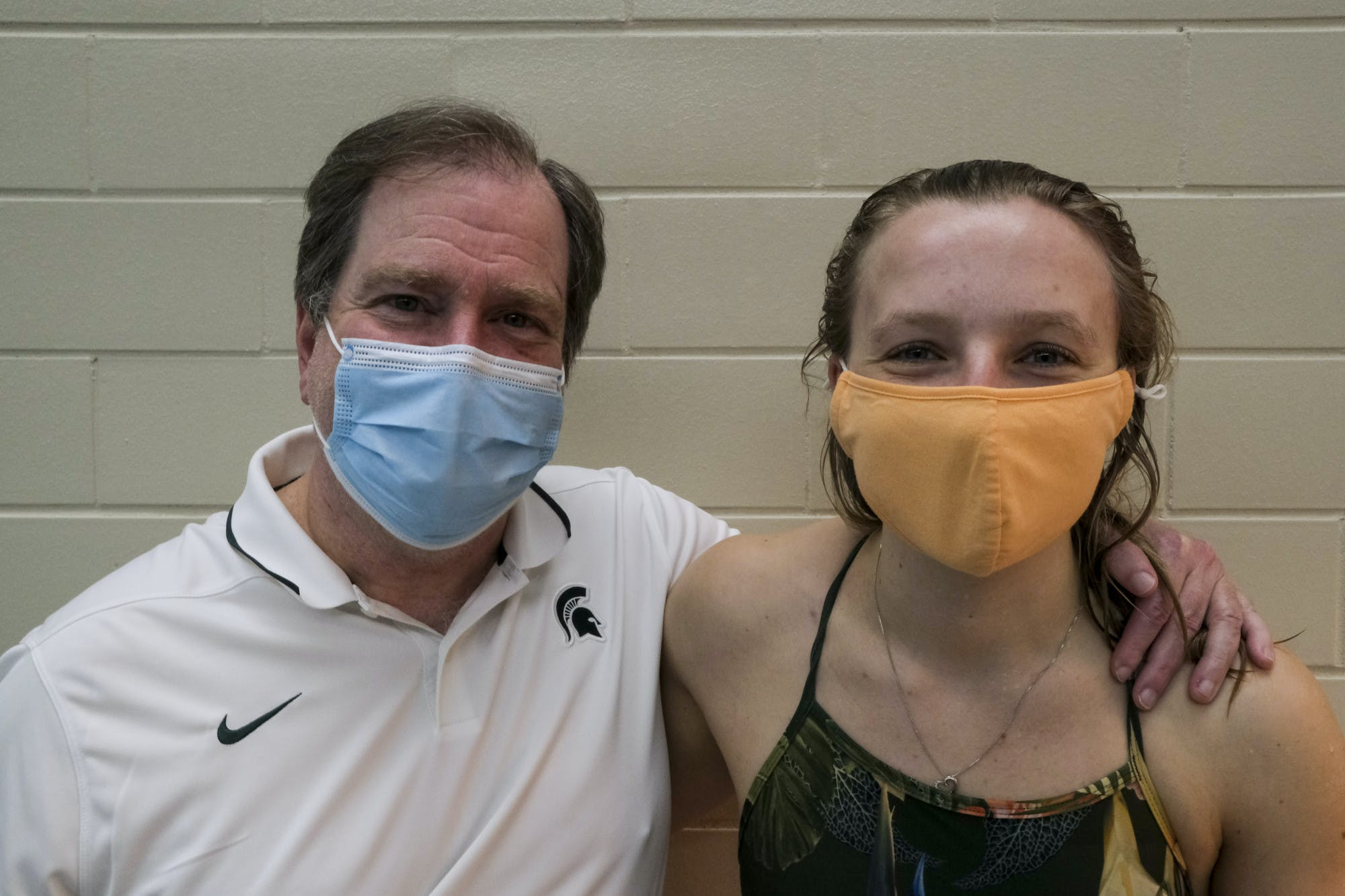 Two people wearing face masks pose for a photo together with their arms around each other. One wears a polo shirt with the Michigan State Spartan logo on it and the other wears a swimsuit.