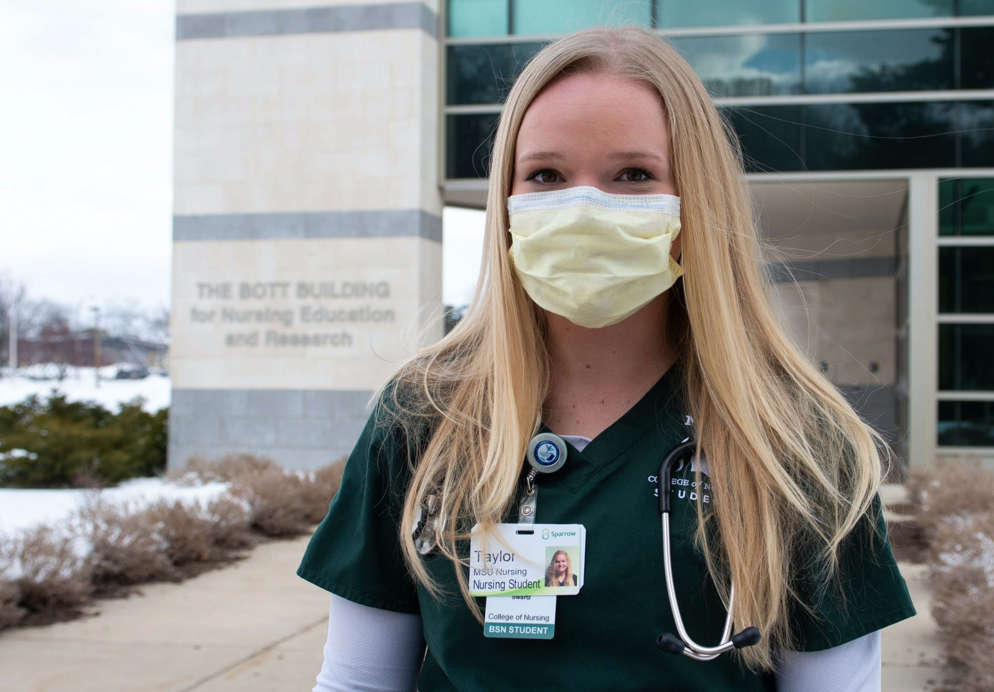 A young woman wearing medical scrubs, a face mask, a name badge and a stethoscope poses for a portrait in front of a building with a sign that reads 'The Bott Building for Nursing Education and Research.'