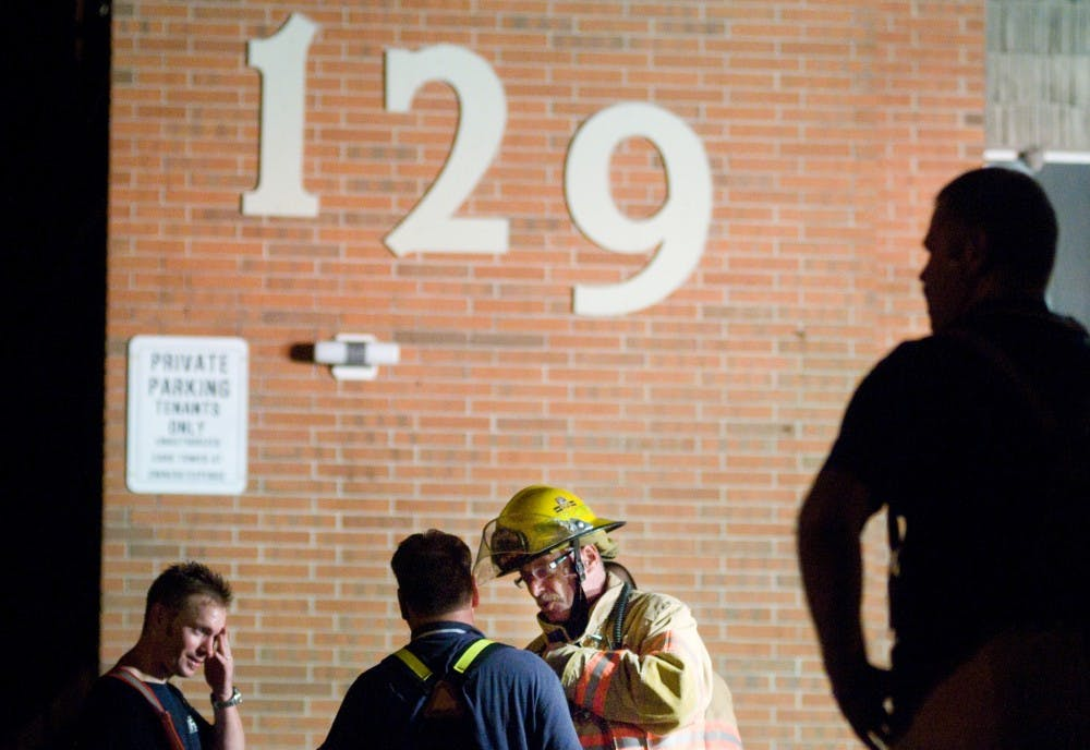 <p>East Lansing firefighter Jim Hudson, center, talks to fellow firefighter Jeff Lund, left center, as first responders clean up and investigate a fire that erupted late Monday night at 129 Burcham Apartments. Three of 12 units were damaged in the fire but no one was injured, according to a firefighter on scene.</p>