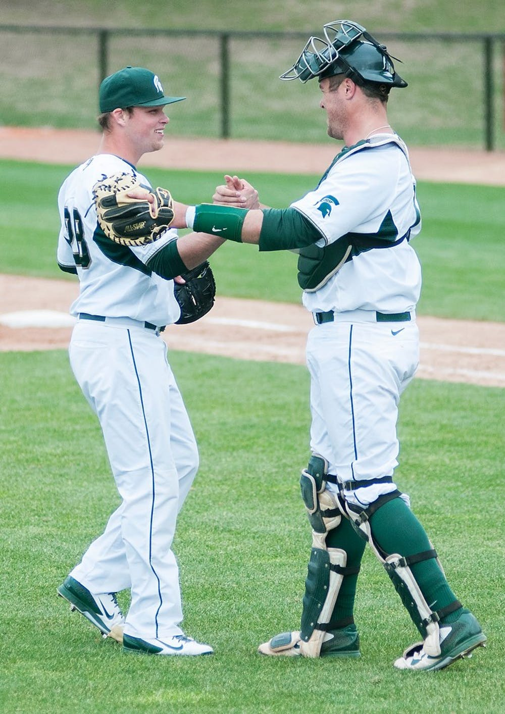 <p>Senior pitcher Chase Rihtarchik, left, celebrates with junior catcher/first baseman Blaise Salter following the game against Toledo on April 22, 2014, at McLane Baseball Stadium at Old College Field. The Spartans defeated the Rockets, 4-2. Danyelle Morrow/The State News</p>