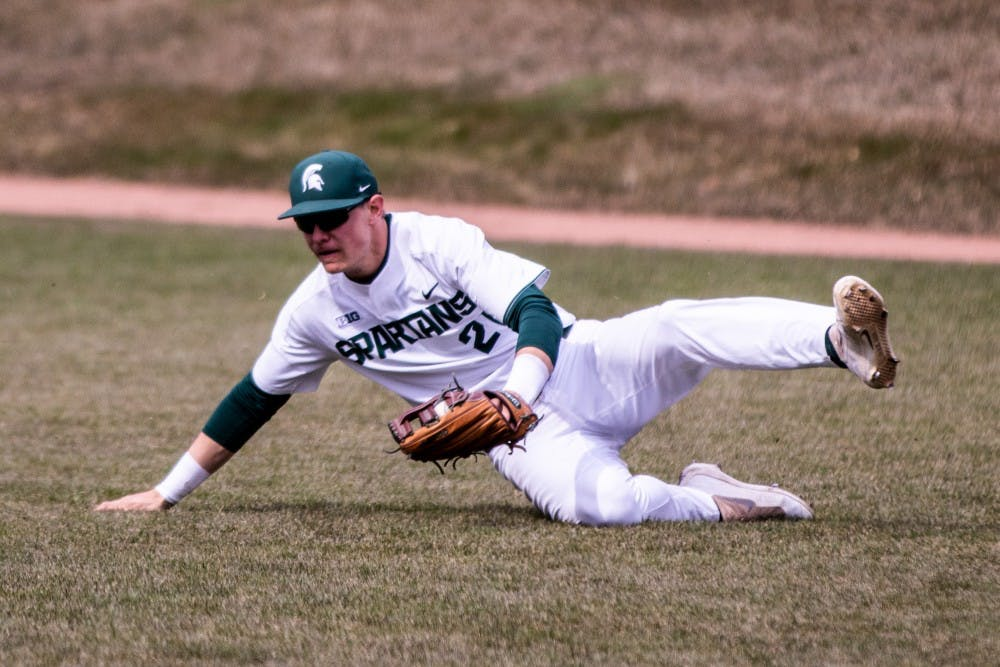 Redshirt junior outfielder Dan Chmielewski (21) slides in the outfield after making a catch during the game against Notre Dame on April 10, 2018 at McLane Baseball Stadium. The Spartans fell to the Fighting Irish, 8-7.
