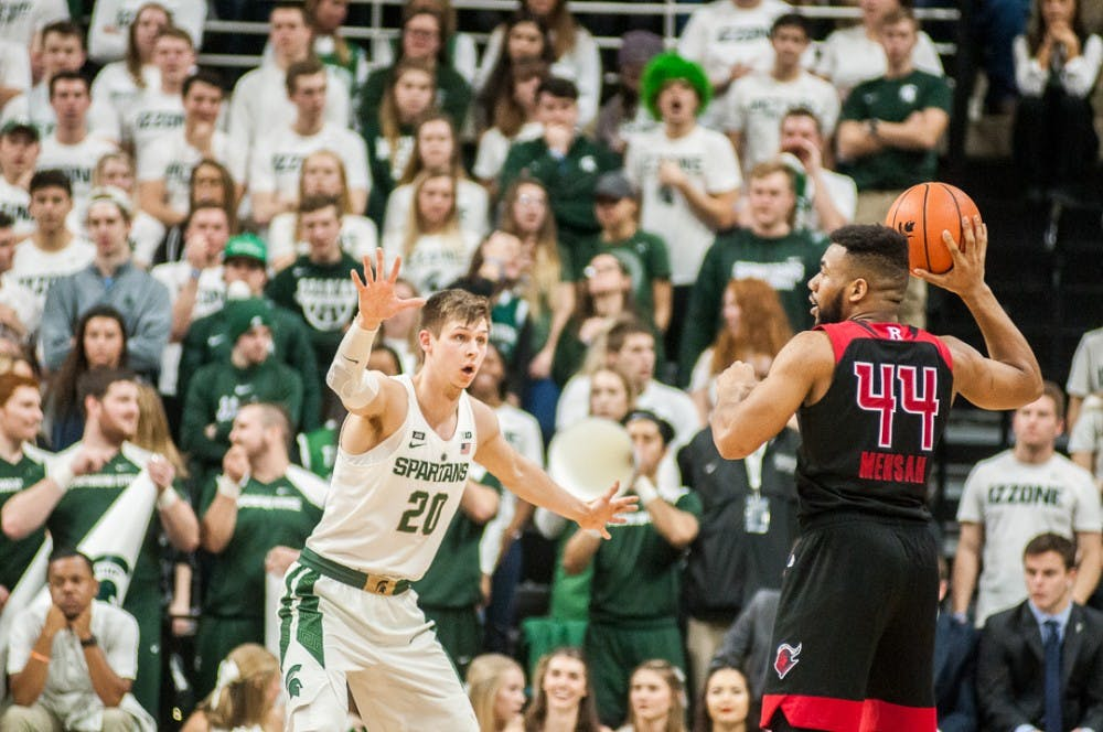 <p>&nbsp;Junior guard Matt McQuaid (20) puts his arms out to block Rutgers junior guard Souf Mensah (44) during the game against Rutgers on Jan. 10, 2018 at Breslin Center. &nbsp;The Spartans beat the Scarlet Knights in overtime 76-72.</p>