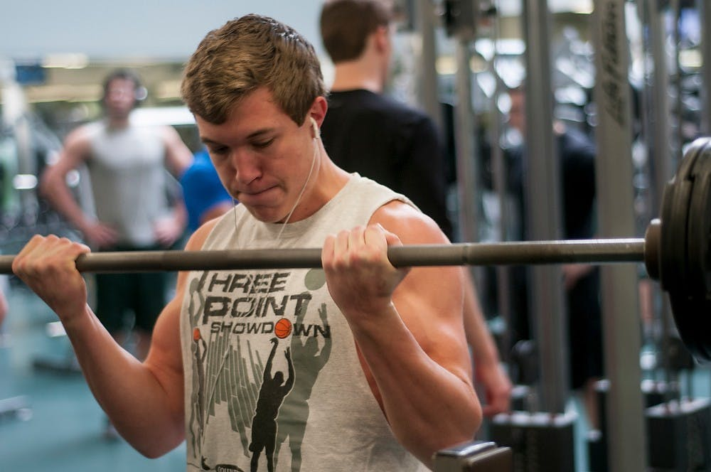 """<p>Mechanical engineering sophomore Conner Archey lifts some weights on Dec. 3, 2014, at IM Sports West. """"Working out most definitely relieves me from a lot of the stress from finals week,"""" Archey said. """"I work about for about an hour, 4 times a week."""" Raymond Williams/The State News</p>"""