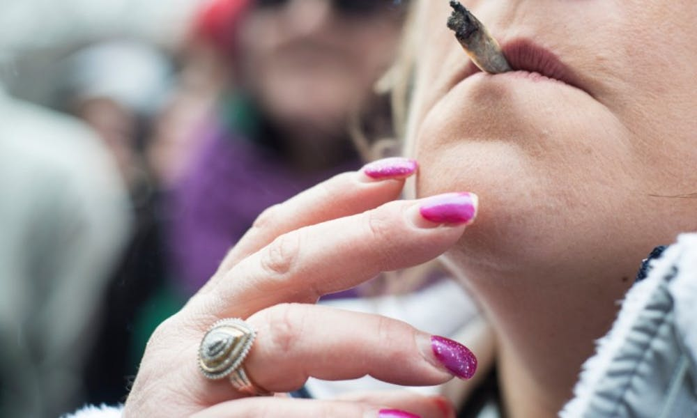 <p>A woman smokes a joint on April 2, 2016 at Hash Bash in The Diag in Ann Arbor, Mich. Hash Bash is an annual event that hosts vendors, music and guest speakers.</p>
