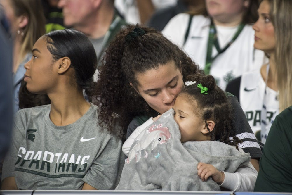 Tamia Todd, fiance of sophomore forward Xavier Tillman (23), kisses her daughter, Ayanna Tillman, 2, during the second half of the NCAA Final Four game against Texas Tech at U.S. Bank Stadium in Minneapolis on April 6, 2019. The Spartans lost to the Red Raiders 61-51.  (Nic Antaya/The State News)