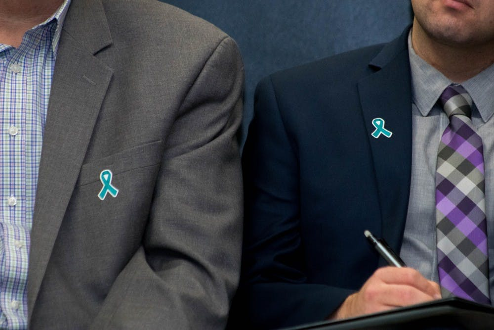 Two members of the presidential search committee wear teal ribbons at the Kellogg Conference Center on Oct. 11, 2018.