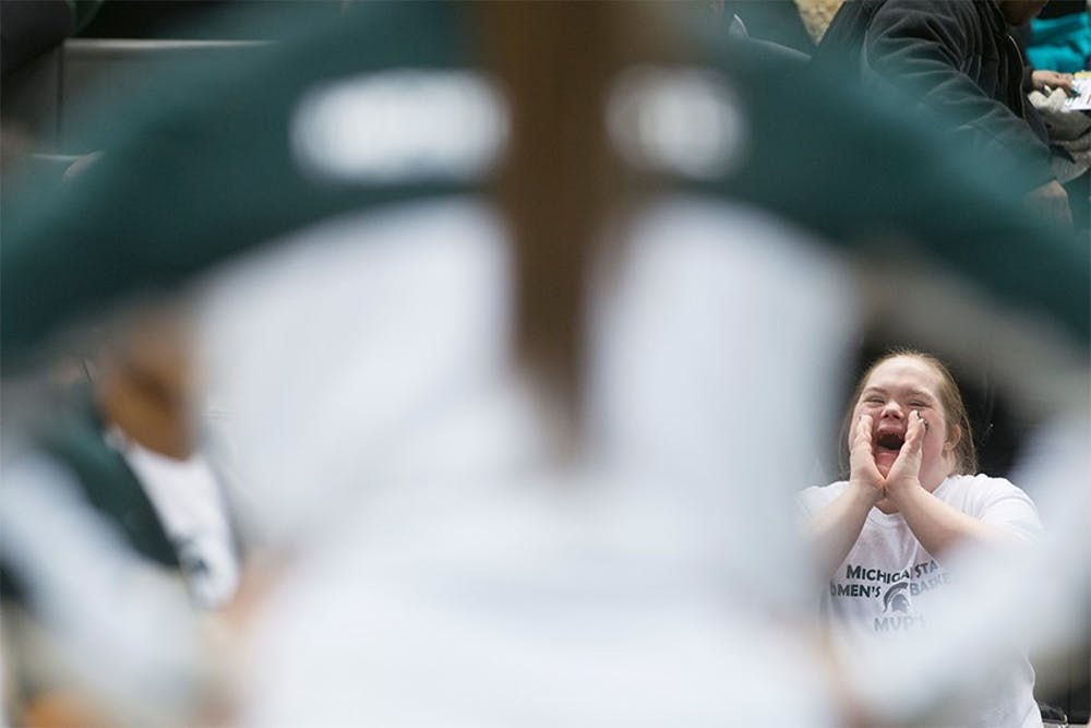 <p>Grand Ledge, Mich., resident Stephanie Russell cheers on the Spartans as the starting lineup is introduced on the court Feb. 24, 2014, before the game against Minnesota at Breslin Center. Russell has attended every women's home basketball game for the past 14 years. Julia Nagy/The State News</p>