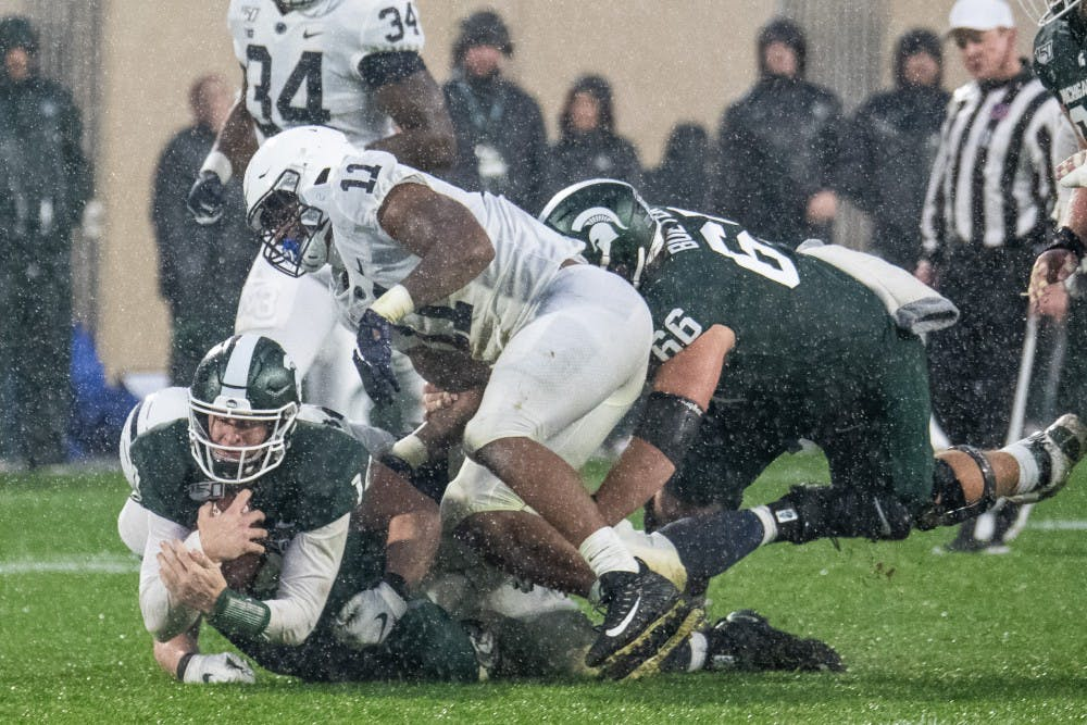 <p>Senior quarterback Brian Lewerke (14) is tackled during the game against Penn State Oct. 26, 2019 at Spartan Stadium. The Spartans fell to the Nittany Lions, 28-7.</p>