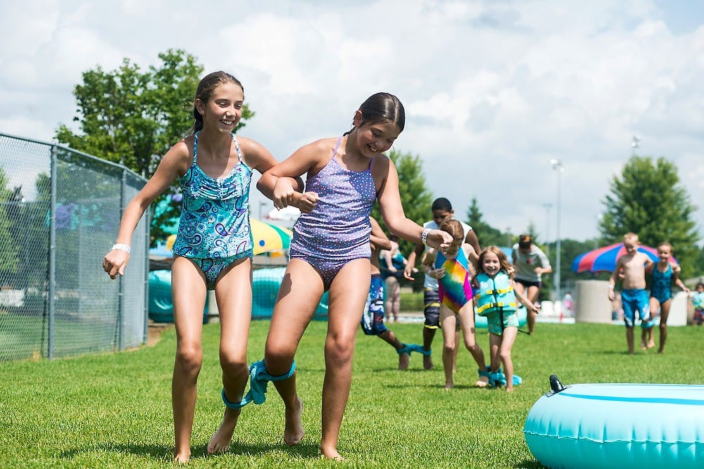 <p>East Lansing residents EmmaRae Vanderbush, 10, left, and Hadley Vanderbush, 11, compete in a three-legged race during the 2014 Summer Splash event, July 30, 2014, at the East Lansing Family Aquatic Center. Activities at the event included a sand castle building contest, a belly flop contest and a balloon toss. Corey Damocles/The State News </p>