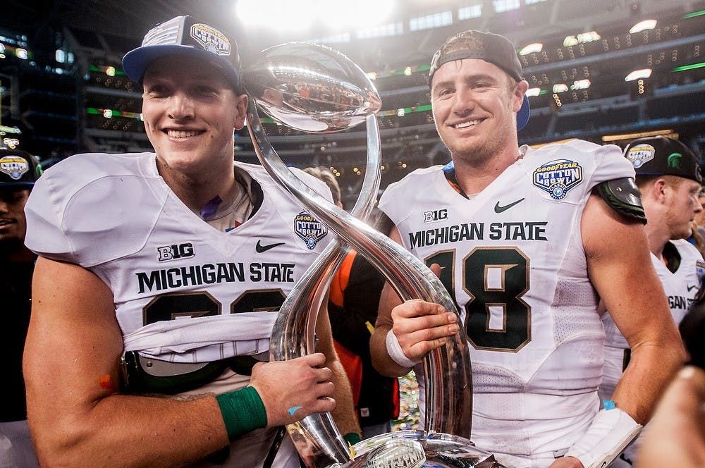 <p>Sophomore tight end Josiah Price and junior quarterback Connor Cook hold the trophy Jan. 1, 2015, after The Cotton Bowl Classic football game against Baylor at AT&T Stadium in Arlington, Texas. The Spartans defeated the Bears and claimed the Cotton Bowl Victory, 42-41. Erin Hampton/The State News</p>