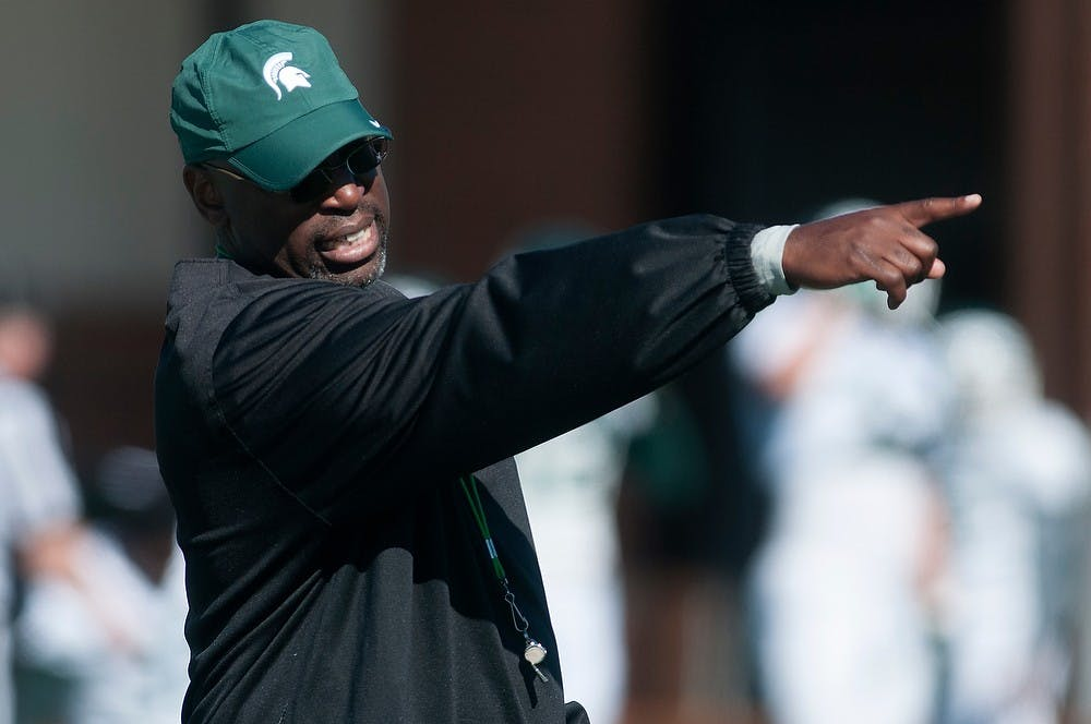 <p>Secondary coach Harlon Barnett leads a practice drill Aug. 14, 2013, at the practice field outside Duffy Daugherty Football Building. Julia Nagy/The State News</p>