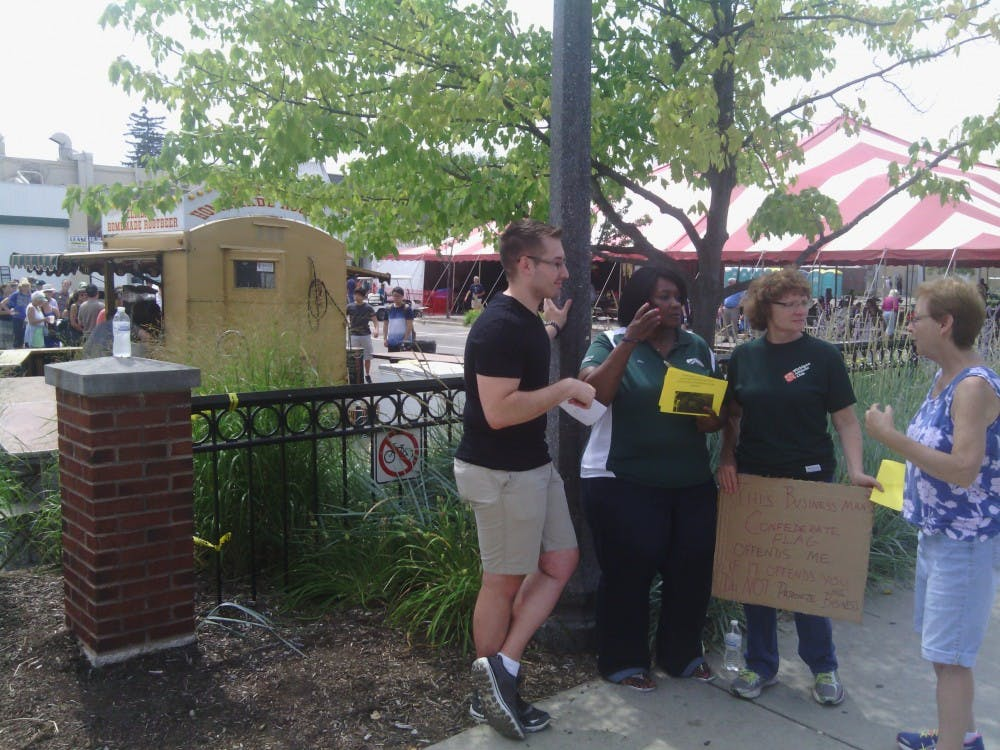 <p>Protesters stand outside Zemer's Homemade Rootbeer stand Sunday at the Great Lakes Folk Festival in East Lansing. The individuals are protesting Zemer's public display of a Confederate flag. Ryan Squanda/The State News</p>