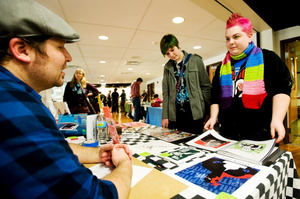 From left, Ann Arbor, Mich. comic artist Denver Brubaker talks with Bath, Mich. resident Maggie Cummings, 16, and biomedical laboratory operations sophmore Ryo Paclot Saturday morning at the LookOut! gallery inside Snyder-Phillips Hall. The two-day event brought comics artists, scholars and fans to MSU, home to the largest public collection of comic books, to celebrate the art of graphic storytelling. Justin Wan/The State News