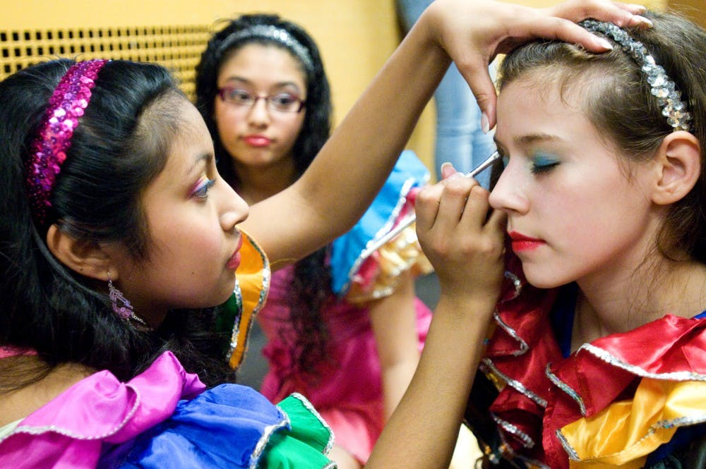 Lansing resident Lena Garcia, 16, left, puts eyeshadow on Lansing resident Emily Sanchez-Weiss, 12, while Lansing resident Thalia Esparza, 14, watches before the girls go on stage to dance for the crowd that gathered at the annual Dia de la Mujer conference Saturday at Kellogg Center. The event is held to celebrate Chicana and Latina women and their accomplishments. Kat Petersen/The State News