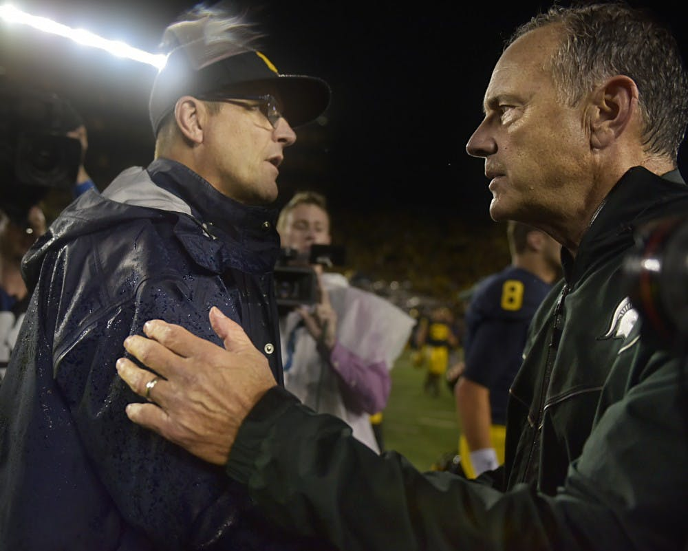 Michigan Head Coach Jim Harbaugh, left, and Head Coach Mark Dantonio shake hands after the game against Michigan on Oct. 7, 2017 at Michigan Stadium. The Spartans defeated the Wolverines, 14-10.