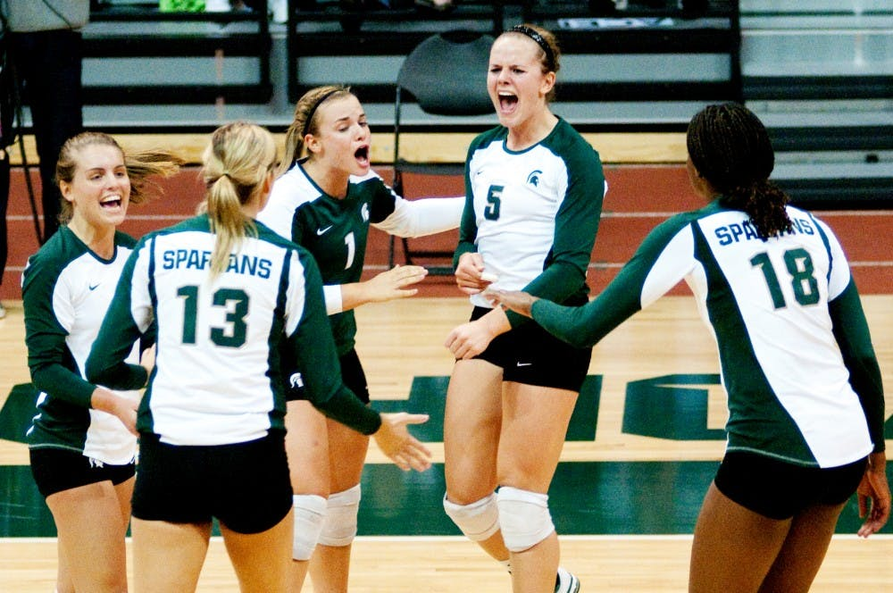 Senior outside hitter Jenilee Rathje celebrates with her teammates after Michigan State scored a point against Ball State. The Spartans defeated Ball State, 3-0, on Friday night on their way to winning the Spartan Invitation this past weekend at Jenison Fieldhouse. Josh Radtke/The State News