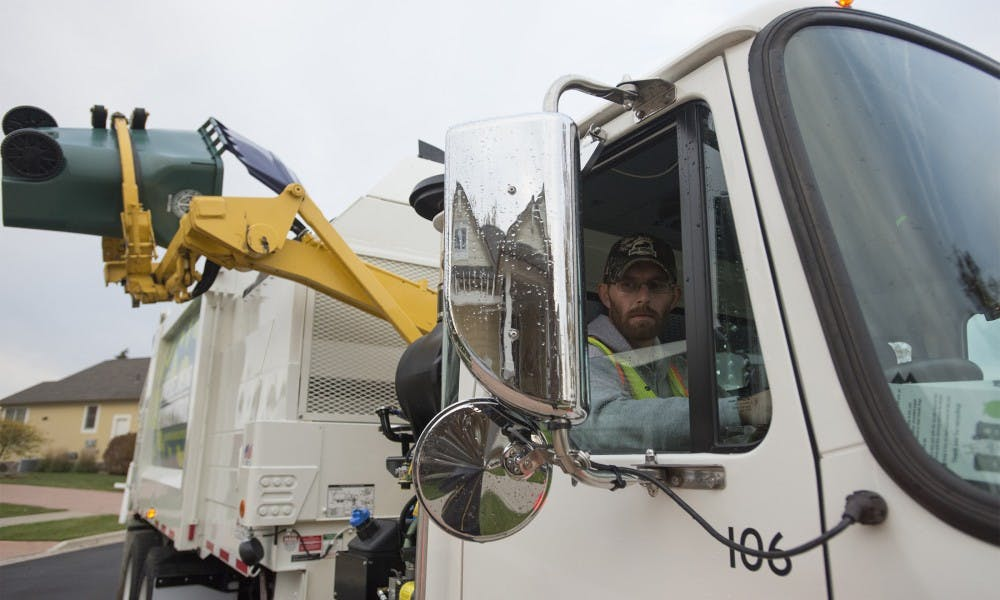 <p>East Lansing Department of Public Works worker Shaun O'Berry watches as trash is poured into his truck on Oct. 22, 2015 in East Lansing. </p>