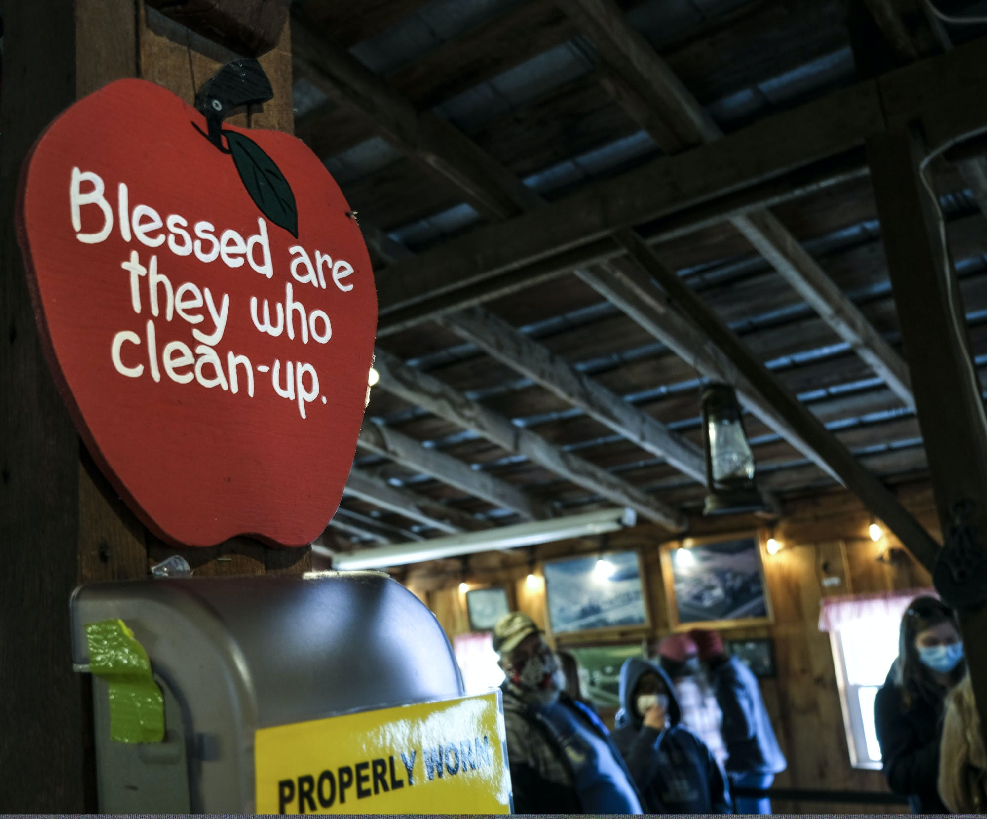 A sign shaped like an apple reads, Blessed are they who clean-up.