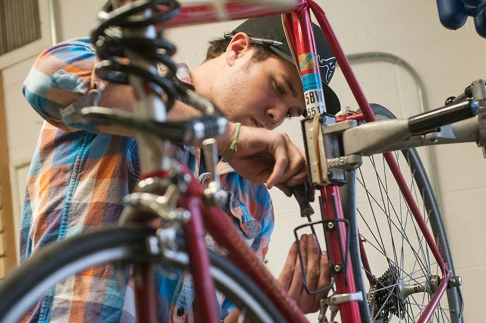 """<p>Education junior Ryan Erxleben replaces the crank on a bike Nov. 18, 2013, at the <span class=""""caps"""">MSU</span> Bikes Service Center, 434 Farm Lane. The bike needed repair after the rider was hit by a turning car on the north side of campus. Margaux Forster/The State News</p>"""