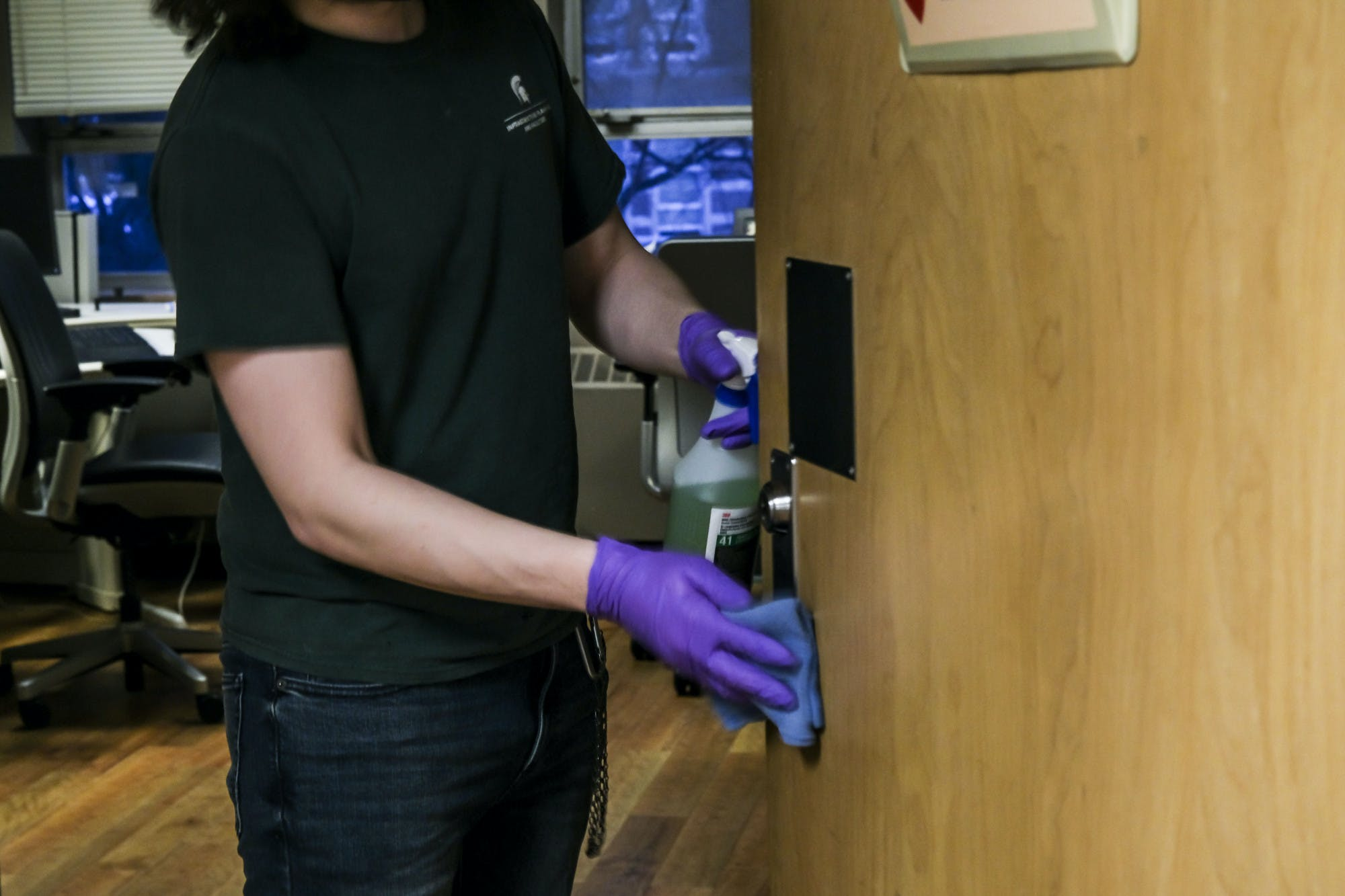 A person wearing purple medical gloves uses a rag to wipe down a doorhandle while holding a cleaning spray. The person's face is not visible.