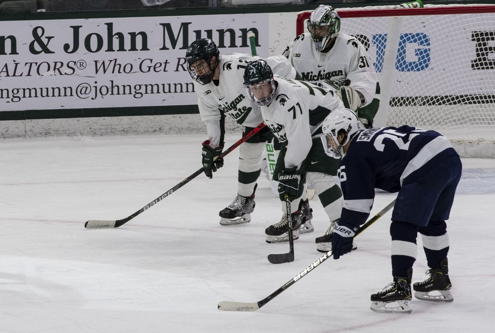<p>Senior right wing Logan Lambdin (71), alongside his teammates, watch for the next move from Penn State as the puck is dropped. Michigan State fell to Penn State 2-1 Jan. 25, 2020.</p>