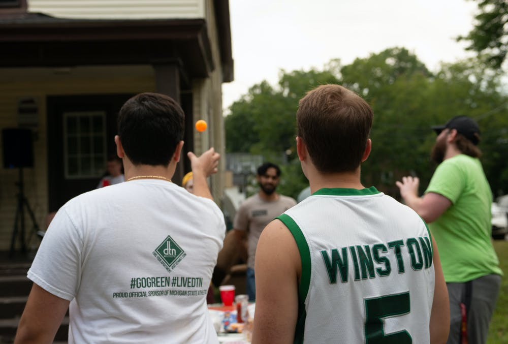 People play beer pong at a tailgate on M.A.C. Ave. in celebration of Michigan State's first football game on Sept. 3, 2021.