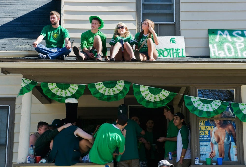 Top left, philosophy junior Ryan Lemasters, education junior Eric Gates, per-nursing sophomore Morgan White and no-preference freshman Emily Wesley sits on the roof of 204 Beal Street on Saturday afternoon during St. Patrick's Day. Thousands of students crowd the streets of East Lansing in celebration of the holiday rooted in the Irish traditions. Justin Wan/The State News