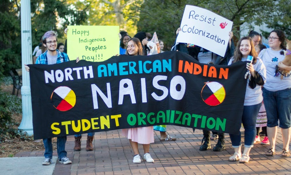 <p>Issac Ward, Tori Ottinger and Jillian Mutchler (left to right) hold up a banner as they march on Oct. 9, from the Beaumont Tower to the Rock on Farm Lane. The march led to an event at the Rock in celebration of Indigenous Peoples&#x27; Day.</p>