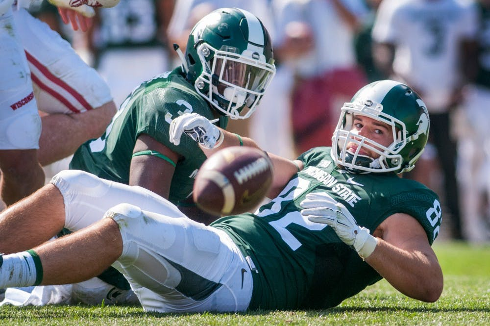 Sophomore running back LJ Scott (3) and senior tight end Josiah Price (82) stare at the football shortly after Scott fumbled the ball during the game against Wisconsin on Sept. 24, 2016 at Spartan Stadium. The fumble was recovered by Wisconsin linebacker Leo Musso and was ran 66 yards for a touchdown. The Spartans were defeated by the Badgers, 30-6.