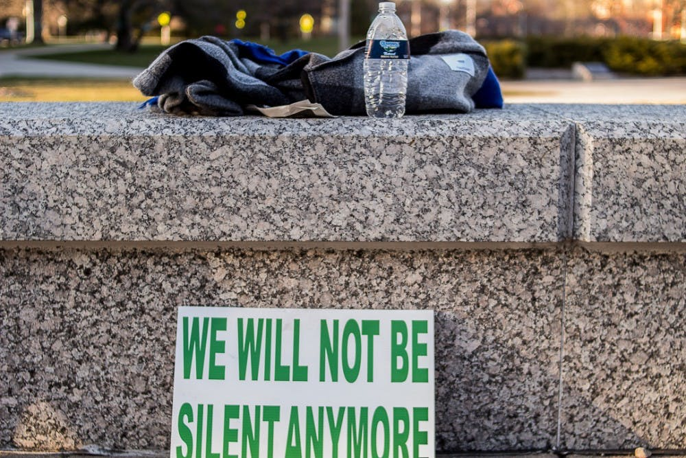A sign rests on the ground after the MSU Rally for Resignations on April 20, 2018 at the Hannah Administration Building. The rally was organized by students and Nassar survivors to call for the resignation of the MSU Board of Trustees.