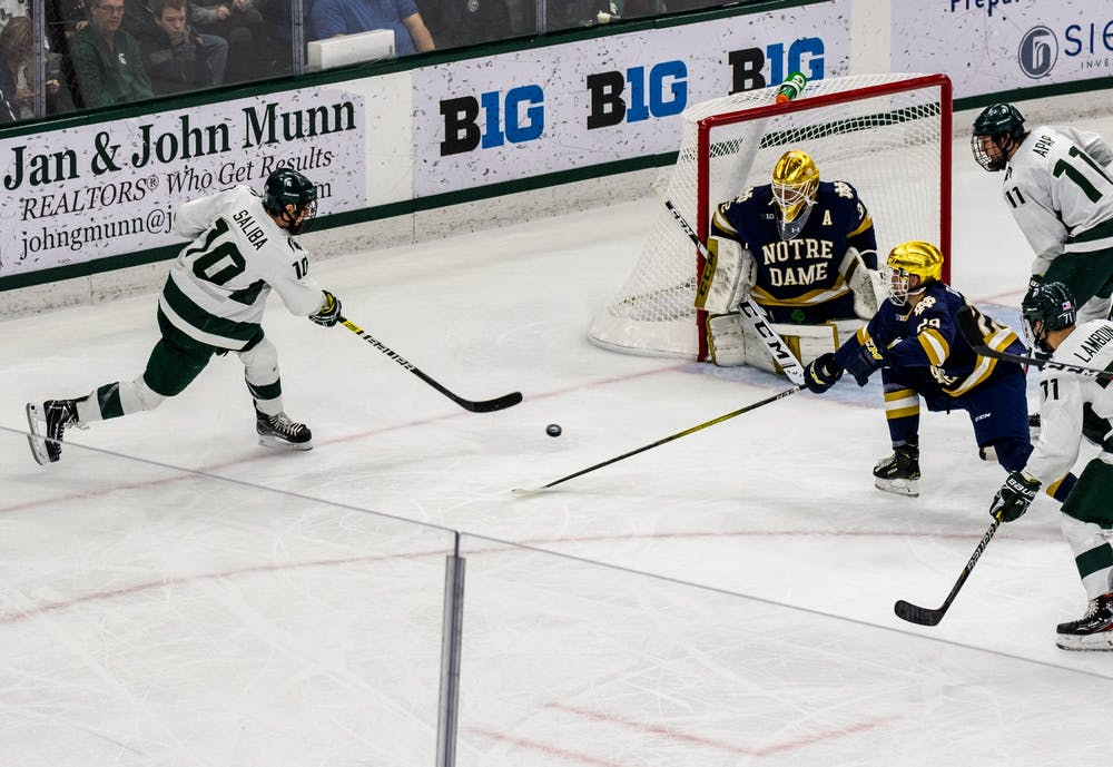 <p>Senior forward Sam Saliba shoots the puck against Notre Dame. The Spartans were defeated by the Fighting Irish, 2-1, at Munn Ice Arena on Nov. 22, 2019. </p>