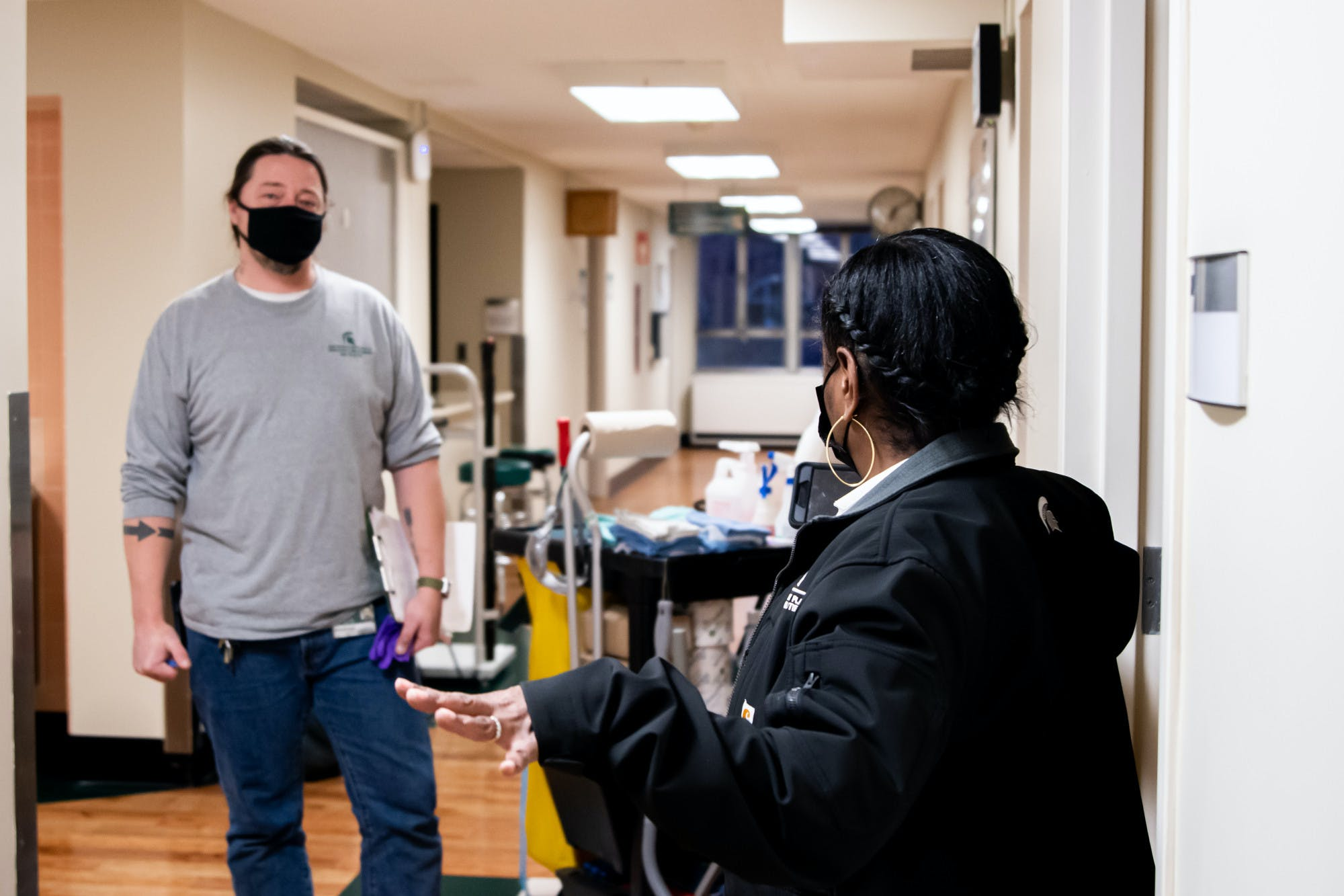 Two people wearing face masks talk to each other distanced in a hallway. Both wear clothing with the Michigan State Spartan logo on them and one person's face is not visible.